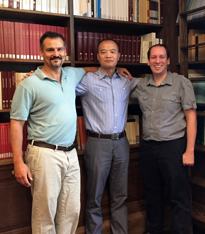 Three men stand and smile in front of a wall of bookcases.