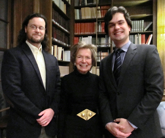 Three people in semi-formal attire stand in a wood-panelled room with bookshelves and smile for the camera.