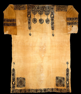 A short-sleeved tunic made of yellowish material is photographed lying flat. Elaborate patterns in a dark color adorn the top and bottom of the garment, while also ringing the sleeves.