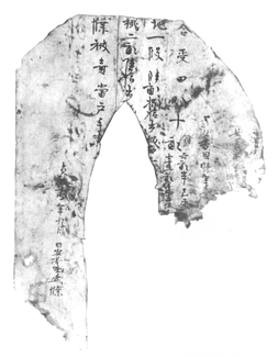 A black-and-white image of a document bearing vertical lines of Chinese characters. Its top corners are rounded and there is an oblong section missing from the middle of the document. Both of the trailing sides are torn off at the bottom.