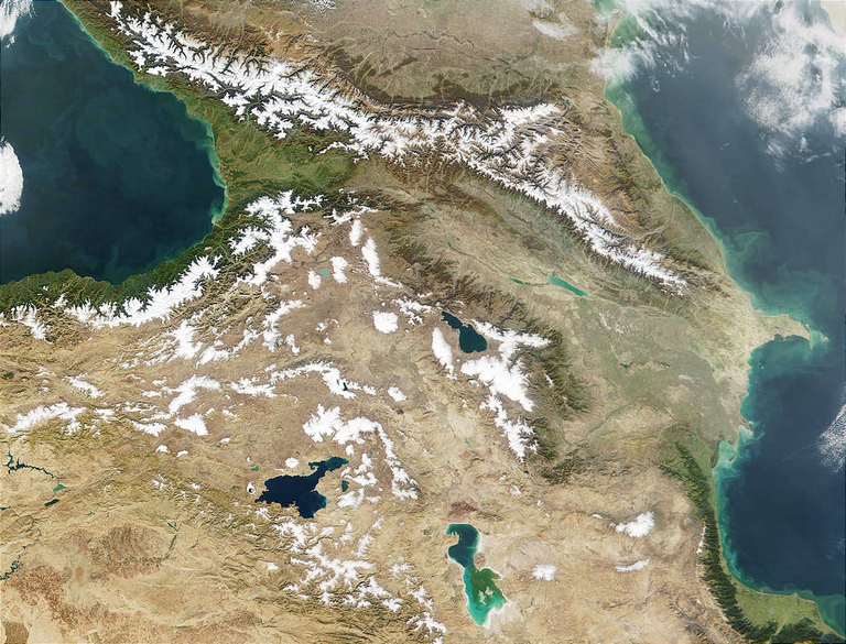 A satellite photo centers on a mountainous region with snow-capped peaks running from northeast to southwest, bordered on both west and east by parts of bodies of water.
