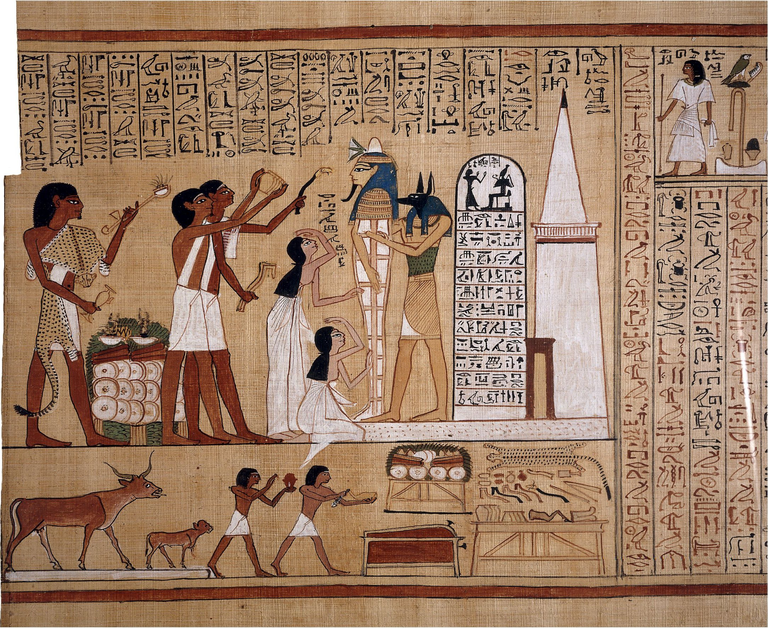 In a colorful Egyptian illustrated papyrus, a jackal-headed humanoid figure holds up a mummy in a standing position while female mourners gesture in front and, behdin them, male figures raise various objects to the mummy's head level. Vertical rows of hieroglyphic text, as well as other illustrations, surround the main image.