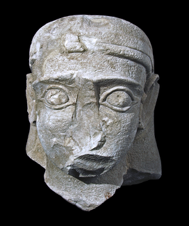 A photograph of a sculpted gray stone head on a black background. The nose and other parts have broken off.