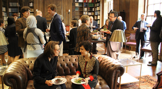 Several groups of people in semi-formal attire carry plates of food while sitting or standing in a wood-paneled room with bookshelves. Bright daylight floods the room from two large windows on the right.