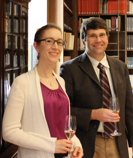 Two people in semi-formal attire stand and smile for the camera in a wood-panelled room with bookshelves.