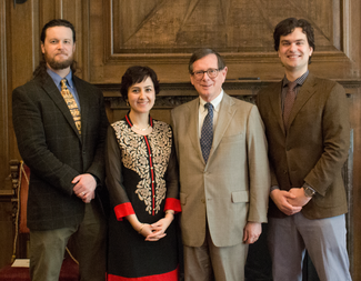 Four people in semi-formal attire stand in a wood panelled room, smiling for the camera.