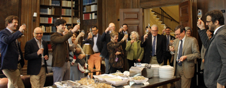 A large group of people in semi-formal attire stand in a wood-paneled room with bookshelves. They surround a rectangular table laden with serving trays of food. They raise wine glasses in a toasting gesture.