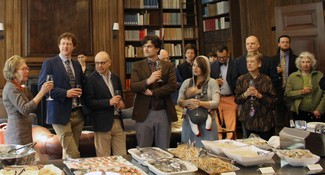 A large group of people stand in a wood-paneled room with bookshelves along and behind a table filled with food. A woman on the left raises a wine glass in a toasting gesture.
