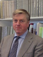 A man wearing a suit and tie looks into the camera. There is a wall of bookshelves behind him.