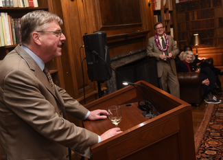A man in a suit and tie speaks from a podium. The photograph is taken from the side and a bit behind him. Beyond him, one can see a wood-paneled room with bookshelves and a large fireplace. Another man stands, and a woman sits, listening.