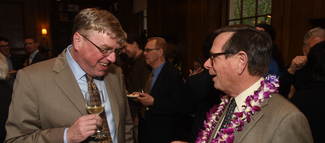 Two men wearing suits and holding wine glasses smile and speak to each other. The man on the left holds a glass of white wine. The man on the right is wearing a necklace of purple and white flowers.