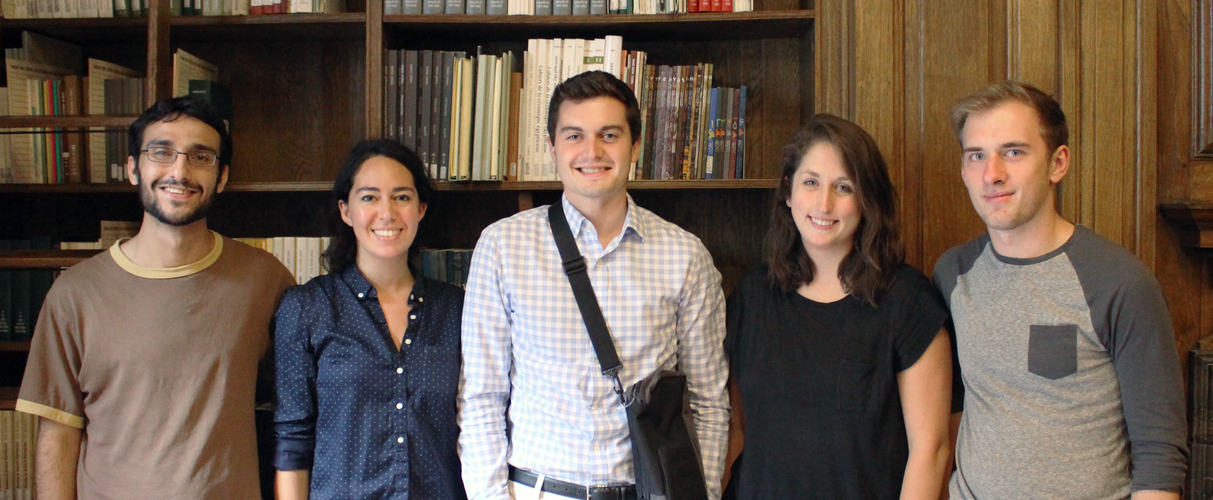 Five people wearing informal dress pose standing for a photograph in a wood-paneled room with bookshelves behind them.