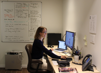 A woman sits at a desk on which several computers, monitors and other technical devices can be seen. On the wall behind, a whiteboard holds notes in multiple colors of ink. On the floor below it, another computer sits with keyboard and other components stacked on top of it.