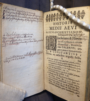 """A photo shows facing pages of a book, which is opened to an angle of about 90 degrees. On the left, one can see hand-written text in black ink with red underlines on an otherwise blank page. On the right, a decorative border appears at top, with the title (HISTORIA MEDII AEGIV SAECVLO CHRISTIANO IV.) below that. Then an elaborate captial D beginning the word """"Diocletiano"""" which initiates a block of text. Below the main text block, 3 formatted footnotes or apparatus components are visible. Some words on this printed page are underlined in red and there is also a handwritten annotation in black in between the title and the first block of text."""