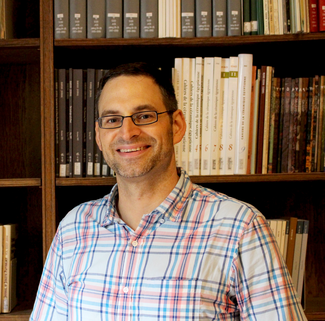 A man smiles into the camera in front of a wall of bookshelves.