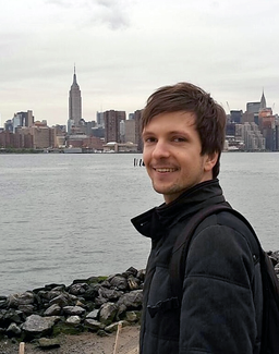 A young man stands, smiling, on a rocky shoreline. The Manhattan skyline--with the Empire State Building prominent--is visible in the distance.