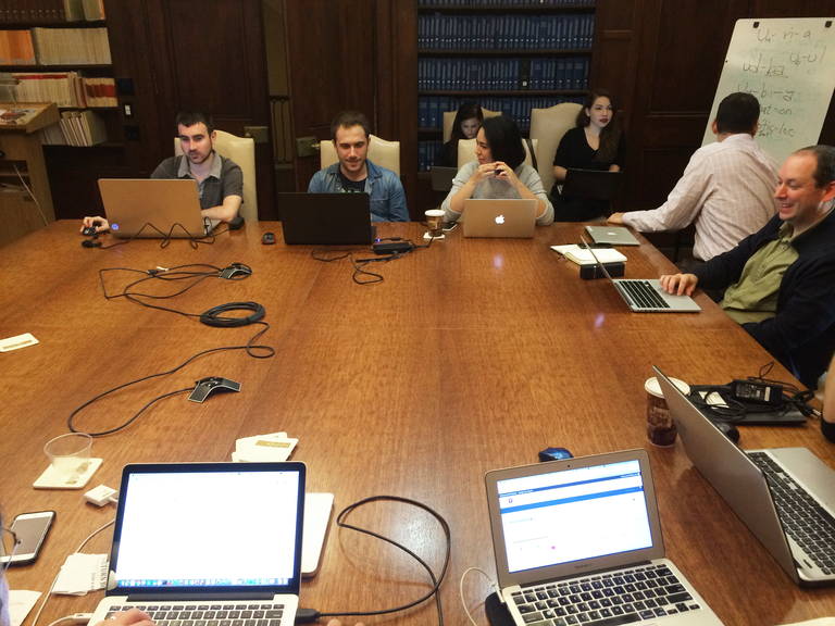 A group of people site, each with an open laptop, around a large square wooden table in a wood-paneled room with bookshelves. Some seem to be working on their computers, others are talking to each other. Two people in the corner are conferring over text written on a whiteboard.