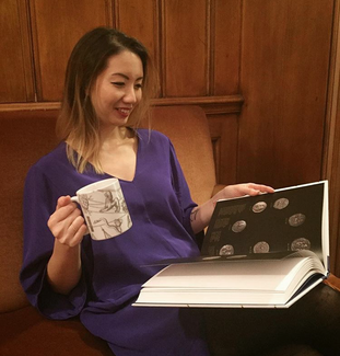 A smiling woman sits on a couch or bench in a wood-paneled room. In one hand, she holds a large, white mug with figures and lines on it in dark gray ink. In her lap is a large book that she holds open with her other hand. A entire page can be seen: it features seven round objects arranged in a circular pattern on a dark background.