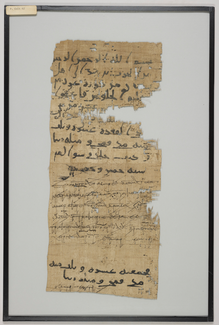 Photograph of a rectangular papyrus document with some parts missing. Multiple texts or hands are visible in the writing: the first text is written in wide strokes of heavy black ink. The second text employs much finer, more closely packed strokes. The two hands recur on the bottom portion of the document.