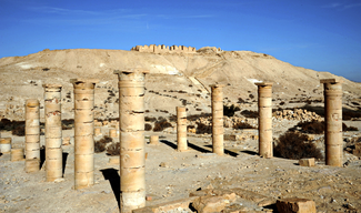 A photograph of an archaeological site in a desert landscape. In the foreground, two series of columns stand in varying stagest of completeness. In the distance, a large hill supports visible remains of large walled structures.