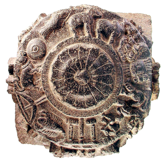 A circular ceramic or stone object with illustrations in relief. In the center, a stylized floral bloom. In the band around the enter, there are depictions of elephants and other animals, tools, anod other objects and figures.