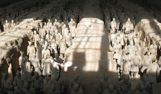 This photograph shows large numbers of ceramic human figures in linear groups in excavated pits, with balks of earth between each.