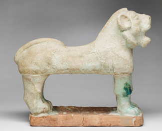 In this photograph, we see from the side a standing, roaring lion made of ceramic and covered in a white glaze.