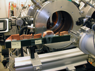 In this photograph, pieces of terracotta-colored ceramic are lined up in a metal tray in front of a complex metal laboratory device consisting of a large metal cylinder behind and a smaller cylindrical device with attached components in the front.
