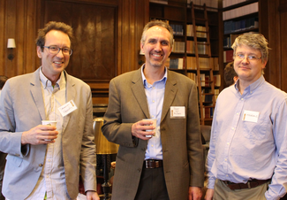 Three people with name tags smile for the camera. Two are holding coffee cups. They are standing in a wood-paneled room with book shelves.