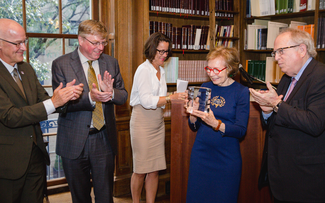 A woman holds a crystal object while four other people stand next to her smiling and applauding. They are in a wood-paneled room with a window and bookcases visible behind them.