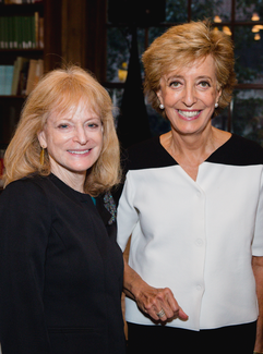 Two women stand and smile for the camera in a wood-paneled room with bookshelves in the background.