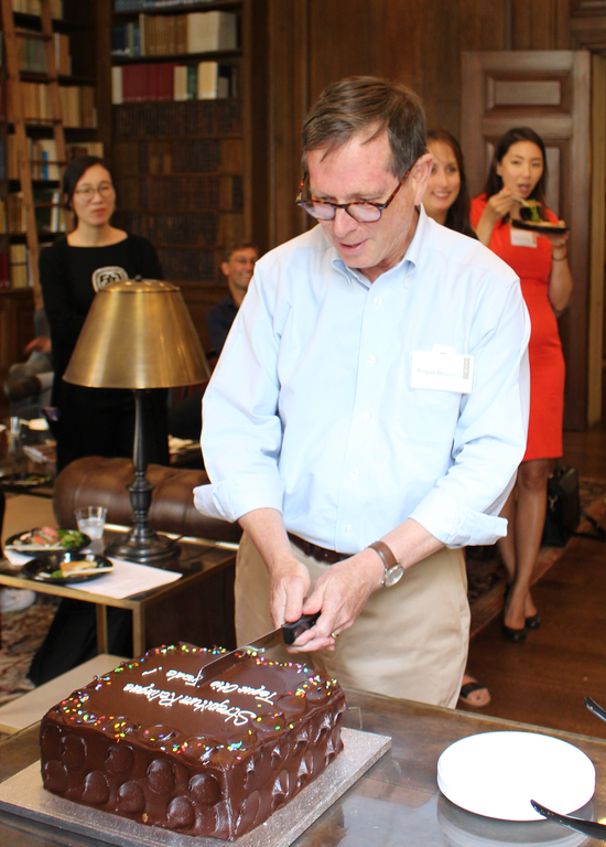 A man smiles and cuts a large, chocolate cake while others stand and sit behind him, smiling. They are in a wood-paneled room with bookshelves.
