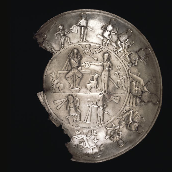A silver plate, missing part of its left rim and illustration band. A band of figures in relief performing various tasks follows the circumference of the plate. In the center, more figures together with plants and animals appear.