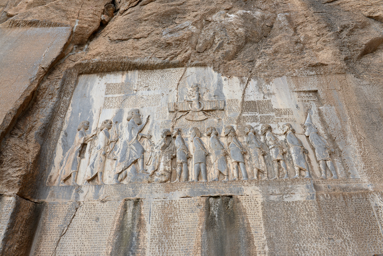 Photo of a rock-cut inscription depicting multiple figures in line with their hands bound behind their backs facing a larger individual who raises a hand. Cuneiform writing appear around and on the figures.