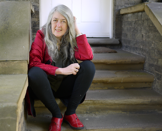 A woman in a red shirt and black slacks sits on a stone stair and looks into the camera.