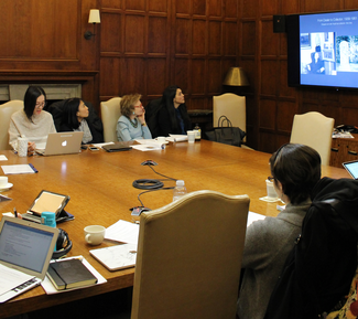 Several people with laptops and notebooks sit at a large square wooden table in a wood-paneled room. One one wall, a large video screen shows a series of indistinct black-and-white photographs.