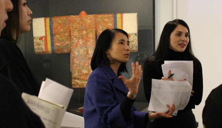 Two women holding papers stand in front of a large panel displaying an article of colorful Asian dress, speaking to other people gathered nearby.