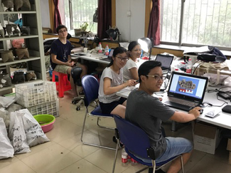 Four people sit at a series of worktables with laptops in a large room with metal shelves and windows. On the shelves are a number of ceramic objects. Plastic crates and polymer bags are lined up on the floor.