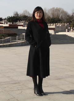 A woman poses in front of what appears to be a monumental stone or concrete plaza and raised area behind.