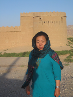 A woman poses in front of what appears to be a contemporaneous or restored mud-brick fortification wall and tower.