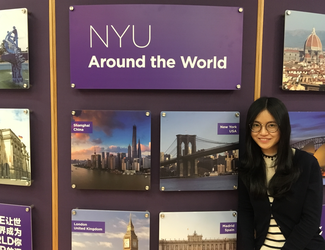 """A woman poses in front of a display that carries a large title """"NYU Around the World"""". The rest of the display is dominated by photographs of cities around the world."""