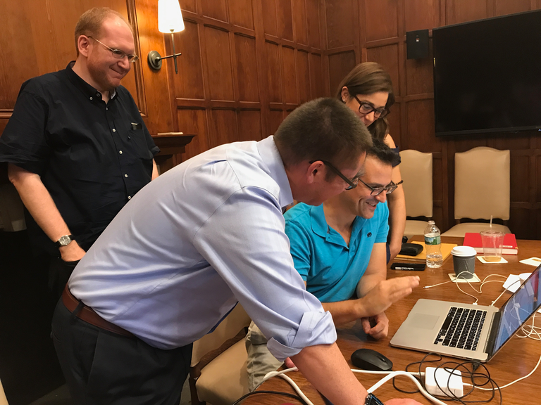 Four individuals cluster around a laptop on a wooden table in a wood paneled room. They appear to be discussing something on the computer