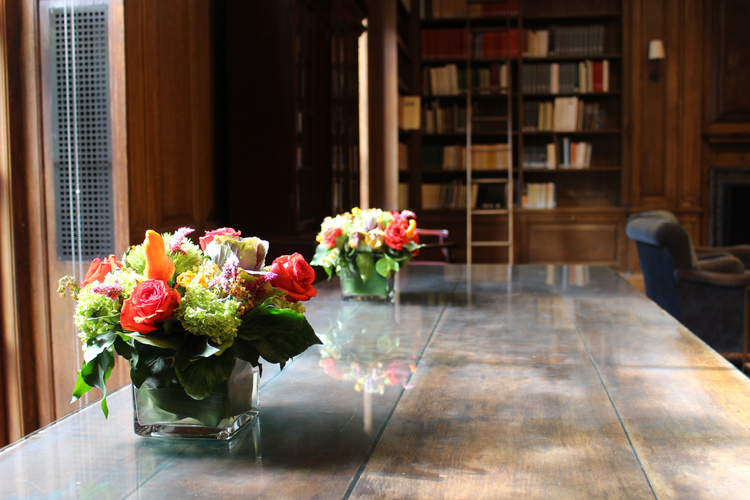 Light from windows at left illuminates a long wooden table bearing two colorful flower arrangements in cubic glass vases. Beyond the table, an upholstered chair and a wall of bookshelves with books can be seen.