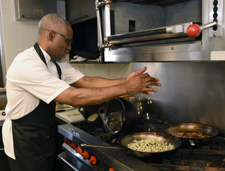 A man wearing an apron works at an industrial gas stove. He reaches out, dropping material into a large skillet on the stove top.