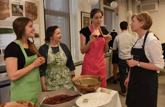 Four people, wearing aprons, interact around a table bearing several large bowls containing liquidnous foodstuffs.