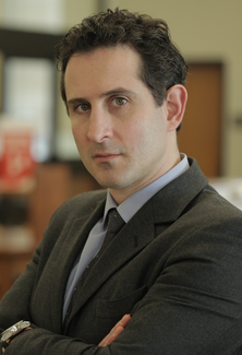 A man in a suit and tie stands at an angle to, but looking into, the camera with his arms folded.