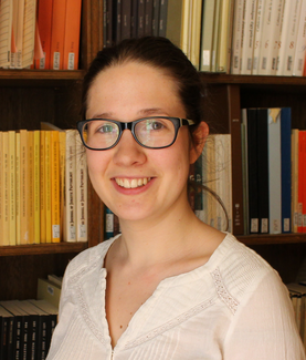 A woman with glasses poses for the camera in front of a bookshelf.