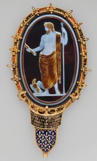 An oval-shaped black, brown, and white cameo in an elaborate gold and enamel frame, depicts a bearded male figure holding a spear and a thunderbolt with an eagle standing near his feet.
