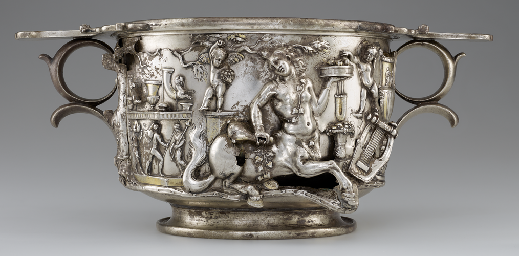 An elaborately decorated silver cup, shaped like a cylinder with two round handles opposite each other just below the lip. The cylindrical cup sits on a slightly smaller base. A female centar, puti, other small figurrees, and musical instruments can be seen in the decoration.