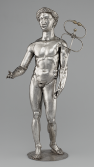 A silver satuette depicting a nude male form holding out his right arm and, in his left hand, grasping a long, narrow wand that ends in two loops, each terminating in a snake head.